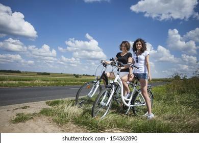 Two pretty girls on bike tour on rock path