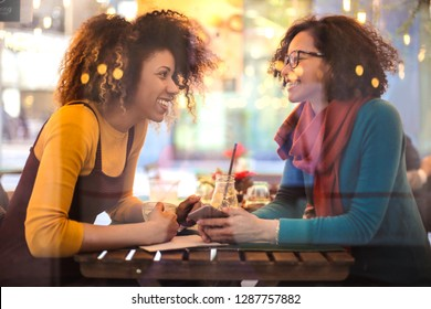 Two pretty girls sitting in a bar, chatting and laughing