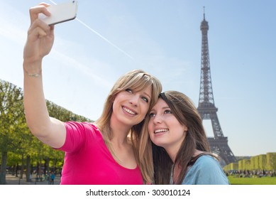 Two pretty girls smiling while taking a selfie in Paris, France on Eiffel Tower background