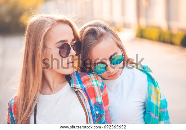 Two pretty girls are standing on the street. Close up. Toning