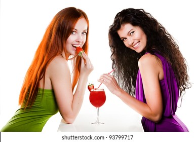 Two pretty girls with a strawberry cocktail