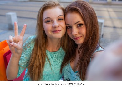 Two pretty girls taking selfie. Urban background. We love selfie photo.