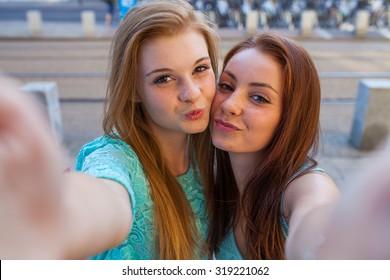 Two pretty girls taking selfie. Urban background. We love selfie photo.