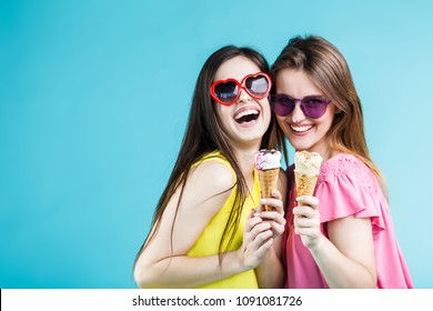 Two pretty happy smiling girls dressed in colorful t-shirts and sunglasses have fun with icecream on blue background, carefree youth concept