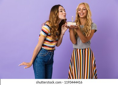 Two pretty happy young girls friends standing isolated over violet background, holding plate with a piece of birthday cake with a candle, blowing candle