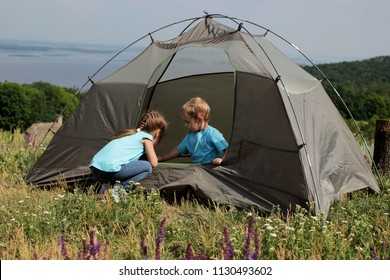 Two pretty kids, brother and sister, learning how to pitch a tent and playing in it near beautiful landscape, active lifestyle, family recreational weekend, summer outdoor