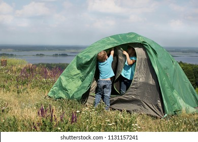Two pretty kids, brother and sister, having fun and learning to pitch a tent near beautiful landscape, active lifestyle, family recreational weekend, summer outdoor