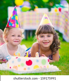 Two pretty little girls celebrating birthday on green grass