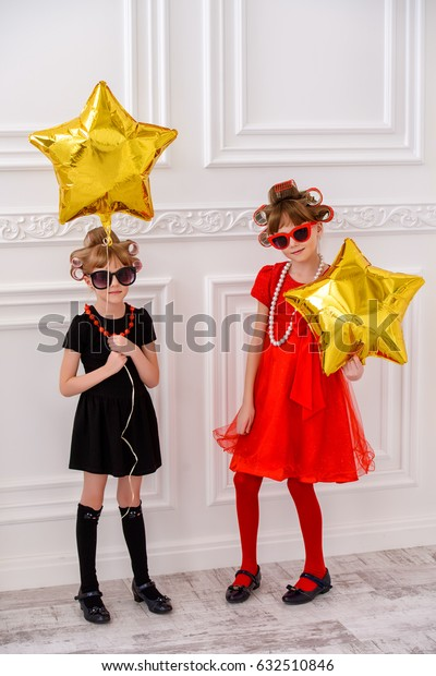Two pretty little girls with curlers in their hair and sunglasses ready for party. Kid's fashion, beauty. Children's party, birthday.