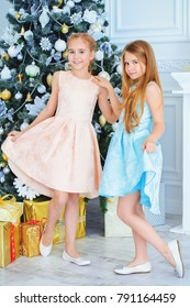 Two pretty little girls dressed in beautiful festive dresses. Kid's fashion.  Luxurious apartments decorated for Christmas. Merry Christmas and Happy New Year.
