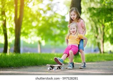 Two pretty little girls learning to skateboard on beautiful summer day in a park. Children enjoying skateboarding ride outdoors.