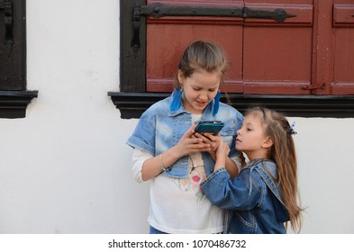 Two pretty little girls  playing and touching smart phone, technology for children