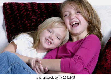 two pretty little girls seated laughing and having fun