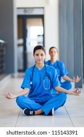 two pretty nurses doing meditation during break in hospital