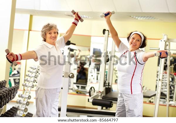 Two pretty senior women exercising with dumbbells