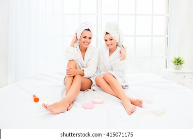 Two pretty sisters in bathrobes with smooth legs siting on bed