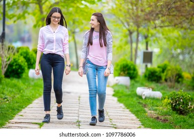 Two pretty sisters girls walking and having fun together in the park in spring.