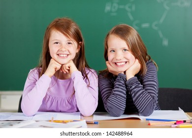 Two pretty smiling girls in school sitting close together behind the table with a chalkboard backdrop