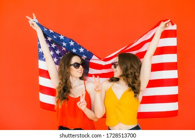 Two pretty stylish girls friends sisters celebrating independence day and having fun over national usa flag on red background