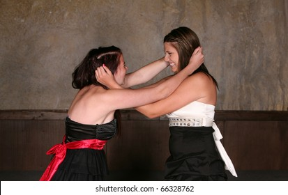 two pretty teen girls fighting physically in dresses