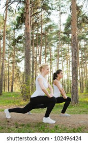Two pretty women with smiles doing stretches in the park
