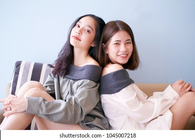 Two pretty young asian girls, one with tan skin color and short hair and one with yellow skin color and long hair, posting for a fashion shoot. Wearing black and white sleeveless dress
