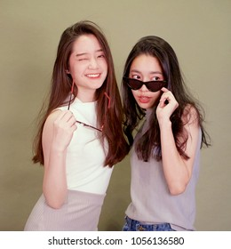 Two pretty young asian girls posting for a fashion shoot. Hilarious and fun. Party concept