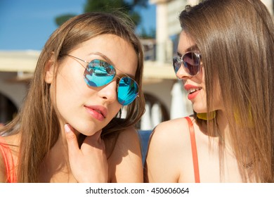 Two pretty young best friends sitting enjoying summer, wearing trendy color swimwear and bright sunglasses