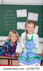Two pretty young girls attending school sitting relaxing on top of a desk in front of the blackboard grinning happily at the camera