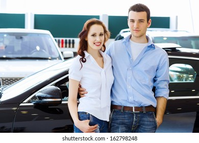 Two pretty young people smiling standing near car