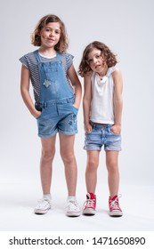 Two pretty young sisters standing side by side with hands in pockets looking at the camera with quiet smiles full length over white