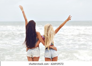 Two pretty young surfers pretty best friend girls having fun on their vacation in Hawaii , mini denim shorts, amazing blonde and brunette hairs, traveling experience, happy emotions.