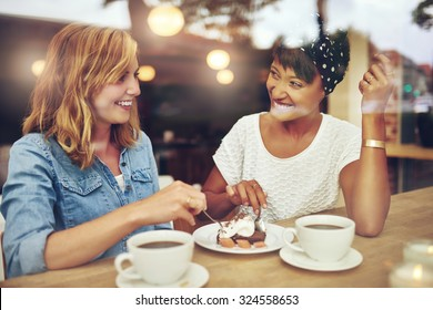 Two pretty young woman enjoying coffee and cake together in a coffee house sitting at a table laughing and gossiping with happy smiles