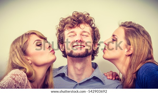 Two pretty young women kissing handsome man. Love triangle.