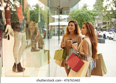 Two pretty young women looking at clothes in shop window