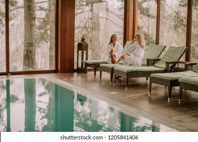 Two pretty young women relaxing on the deckchair by the swimming pool in spa
