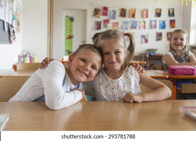 Two primary school children hugging each other in classroom environment