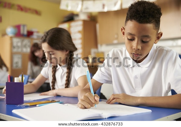 Two primary school pupils at their desks in class, close up