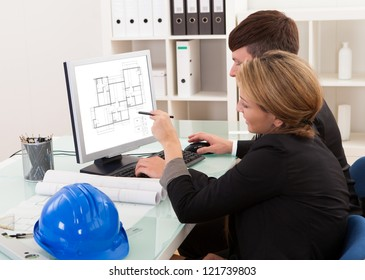Two professional architects or structural engineers sitting at a desk looking at a computer discussing a building plan