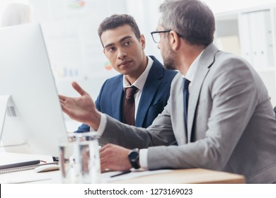 two professional businessmen using desktop computer and discussing project in office