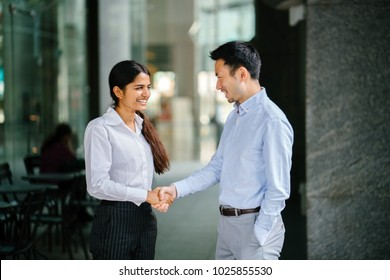 Two professional businesspeople shake hands in an office in the city. An Indian woman shakes hands with a Chinese man in agreement and they are both smiling and professionally dressed.