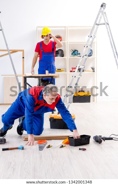 Two Professional Contractors Laying Flooring Home Stock Photo