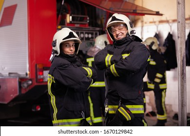 Two professional firefighters with uniforms and protective helmets posing infront of a firetruck.