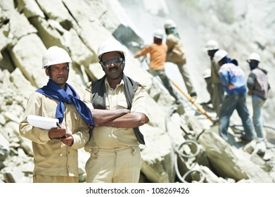 Two professional indian asian engineer builders foremans with plan at mountains construction site