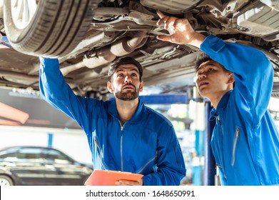 Two professional look technician inspecting car underbody and suspension system by using check list in moder car service shop. Automotive business or car repair concept.