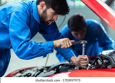Two professional look technician inspecting car engine and lubricant  system by using check list in moder car service shop. Automotive business or car repair concept.