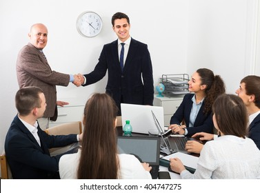 Two professional managers shaking hands at business meeting