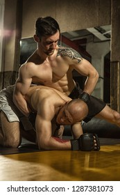 Two professional mixed martial art fighters in gloves and shorts grappling in gym. Sportsman with perfect body and tattoo catching with hands his strong opponent standing on knees and hands.