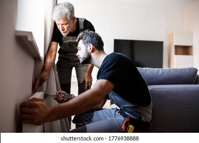 Two professional plumbers, workers in uniform fixing or installing heating radiator. Construction, maintenance and repair concept. Selective focus. Horizontal shot