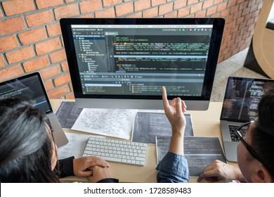 Zwei professionelle Programmierer kooperieren und arbeiten an Web-Site-Projekt in einer Software, die auf Desktop-Computer in Unternehmen, Codes und Eingabe von Datencode, Programmierung mit HTML, PHP und JavaScript.